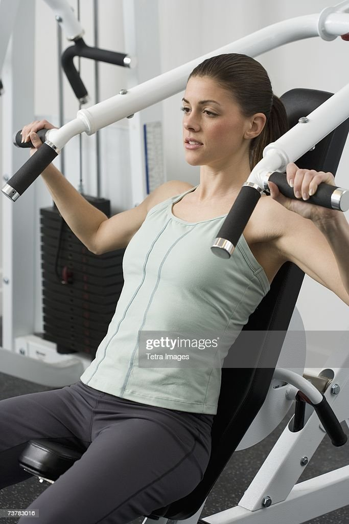 Woman exercising on machine at health club : Stock Photo
