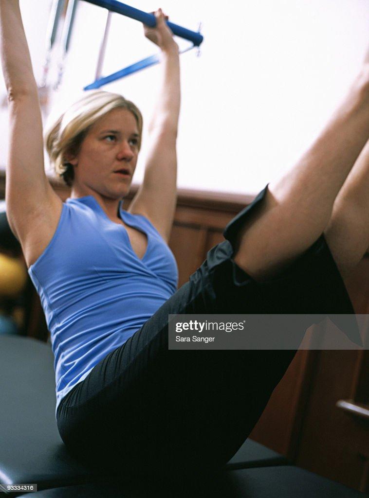Woman exercising on pilates machine