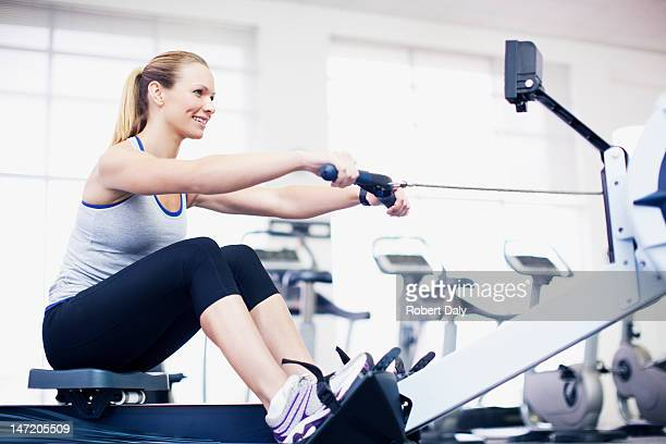 Woman exercising on rowing machine in gymnasium