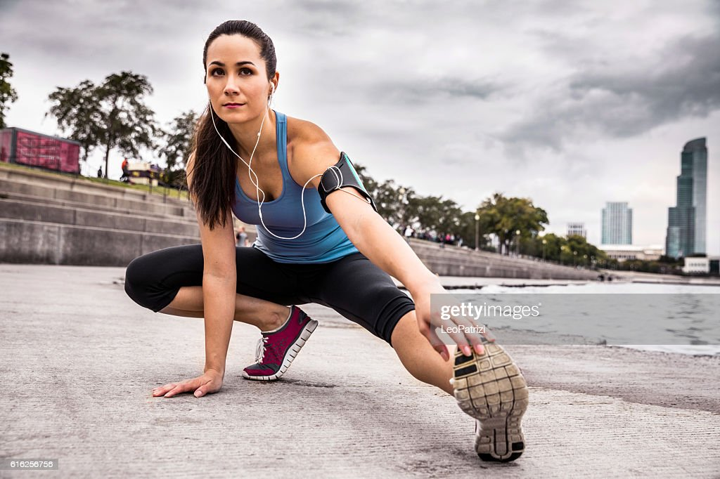 Woman exercising outdoor, stretching post running : Stock Photo