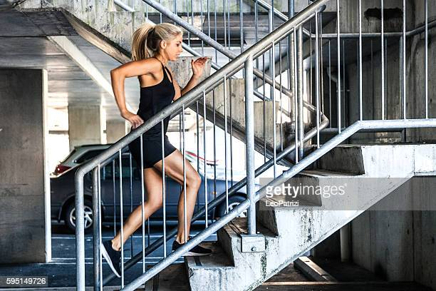 Woman exercising running up on stairs