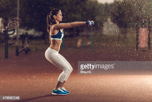 Woman exercising with dumbbells in squat position on rainy day.