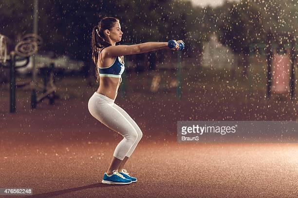 Femme exercice avec haltères en position de squat sur un jour de pluie.