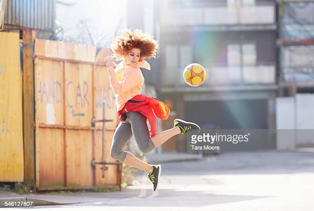 Woman exercising with football in urban street
