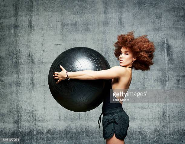 Woman exercising with gym ball in urban studio