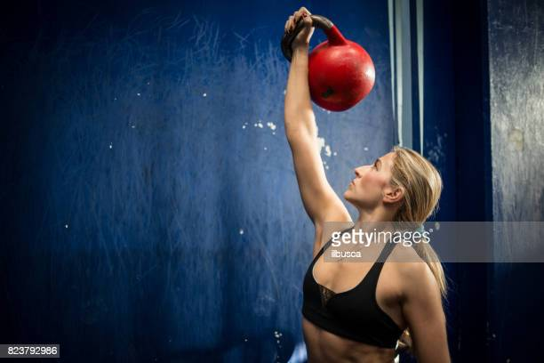 Woman exercising with kettlebell in cross training gym