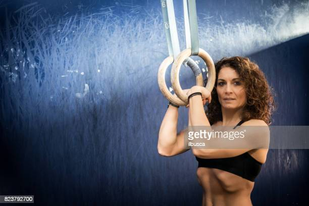 Woman exercising with rings in cross training gym