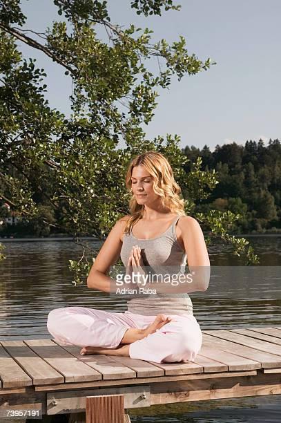 Woman exercising yoga on jetty