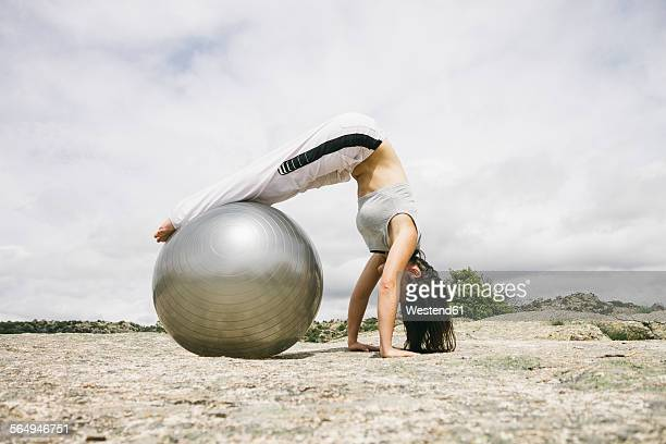 Woman exercising yoga outdoors with gym ball