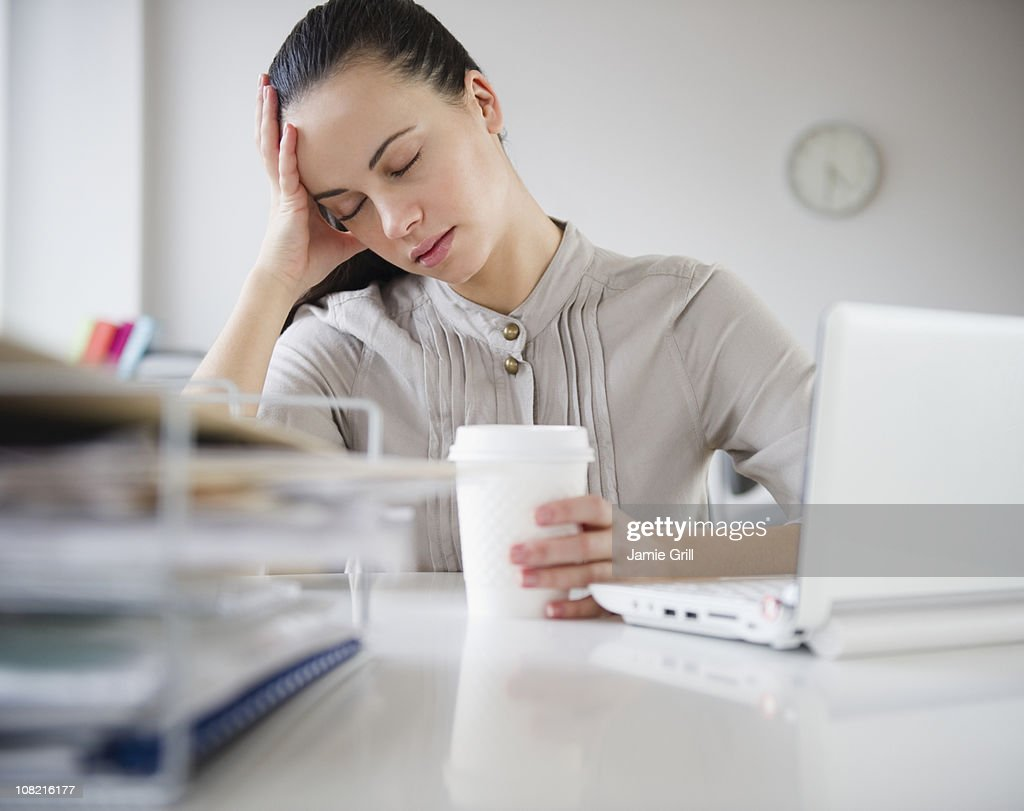 Woman exhausted at desk with coffee : Stock Photo