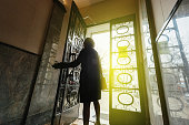Elegant woman wearing French coat walking out the door of a luxury French building - concept for business success, new beginnings and personal success