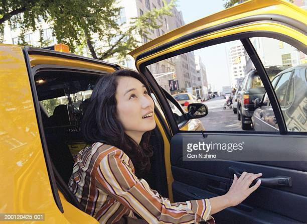 Woman exiting taxi cab, looking upward