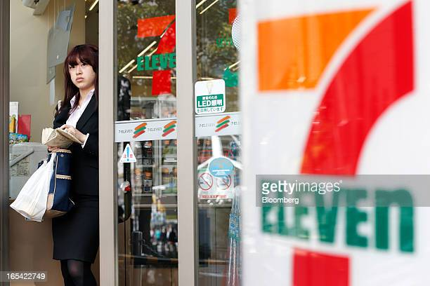 A woman exits a 7Eleven convenience store operated by Seven I Holdings Co in Tokyo Japan on Thursday April 4 2013 Seven I Holdings Co owner of the...