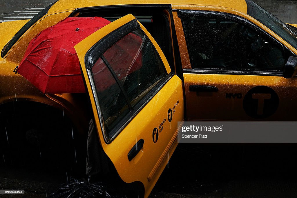 A woman exits a cab with an umbrella during a rain storm on May 8, 2013 in New York City. After experiencing an unusually dry spring in recent weeks, New York was hit with heavy rain Wednesday that resulted in numerous flash floods and heavy downpours.