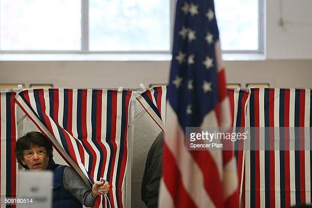A woman exits a voting booth inside of a middle school serving as a voting station on the day of the New Hampshire Primary on February 9 2016 in Bow...