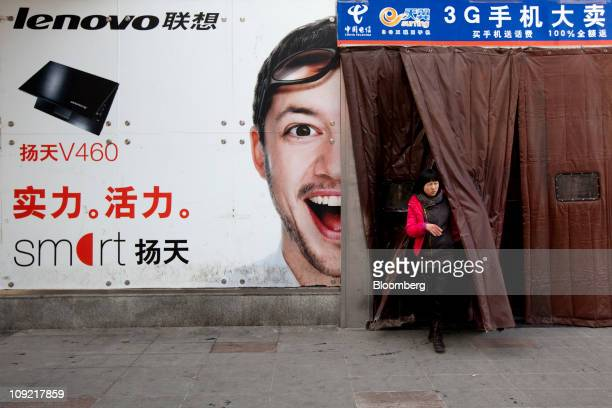 A woman exits past an advertisement for Lenovo Group Ltd at a computer market in Beijing China on Thursday Feb 17 2011 Lenovo Group Ltd China's...