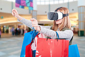 Woman experience shopping online with VR headset inside the mall