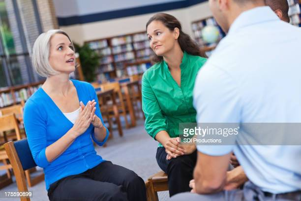 Woman explaining something to her friendly support group
