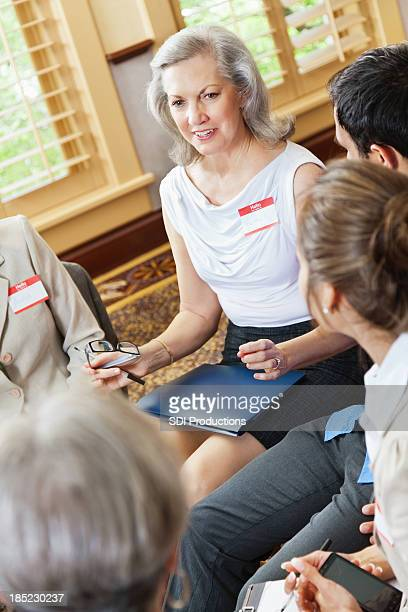 Woman explaining something to support group friends
