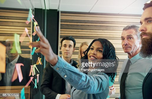 Woman explaining the plan to office team : Stock Photo
