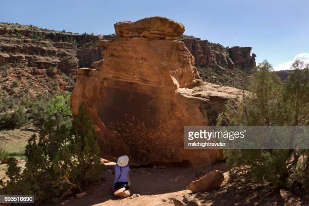 Woman explores Ute Native American petroglyphs Dominguez Canyon Wilderness Colorado conservation area