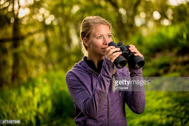 Woman Exploring a Nature Setting with Binoculars