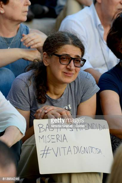 A woman exposes a sign saying 'It's enough male salaries decent life on July 13 2017 in Rome Italy No one is illegal demonstration in Campidoglio...
