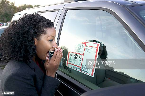 A woman expresses her amazement at the price of a new car in a car lot