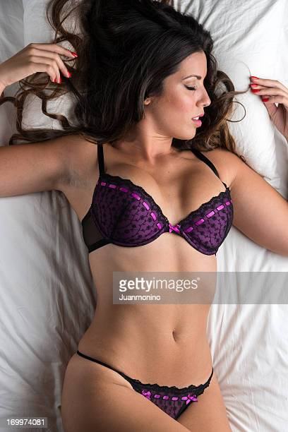 Woman, eyes closed in purple bra and panties laying on bed.