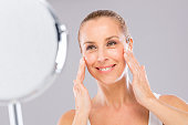 Middle aged woman with care and tenderness face skin looking to the mirror.