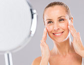 Middle aged woman with care and tenderness face skin smiling to the mirror.