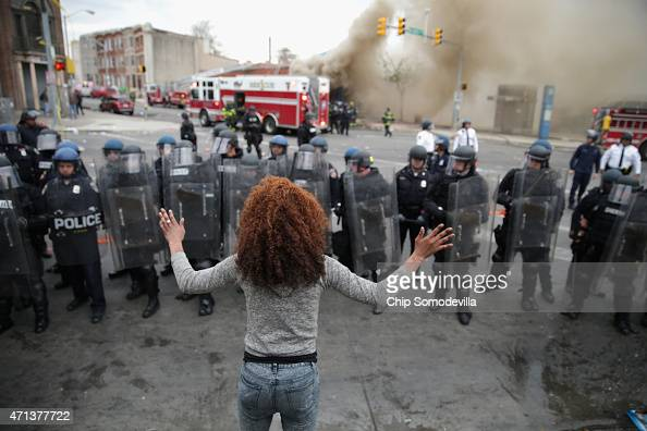 A woman faces down a line of Baltimore Police officers in riot gear during violent protests following the funeral of Freddie Gray April 27 2015 in...