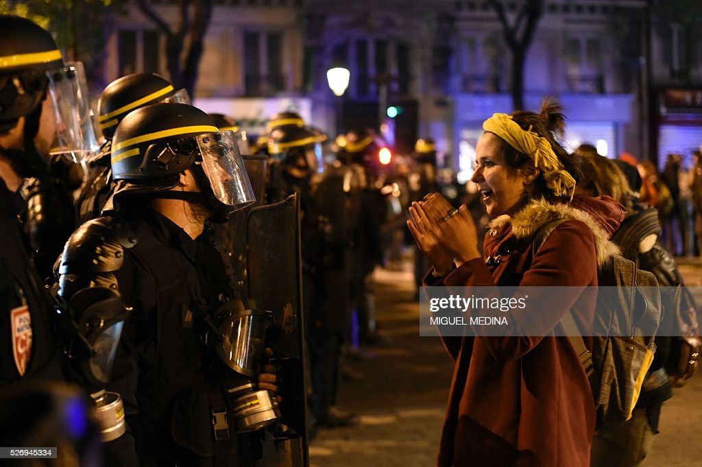 A woman faces French anti riot policemen as they block the access to the Place de la Republique after protesters taking part in the Nuit Debout (Up All Night) movement against the French government's proposed labour reform, being evacuated by police from the Place de la Republique in Paris, on May 1, 2016.