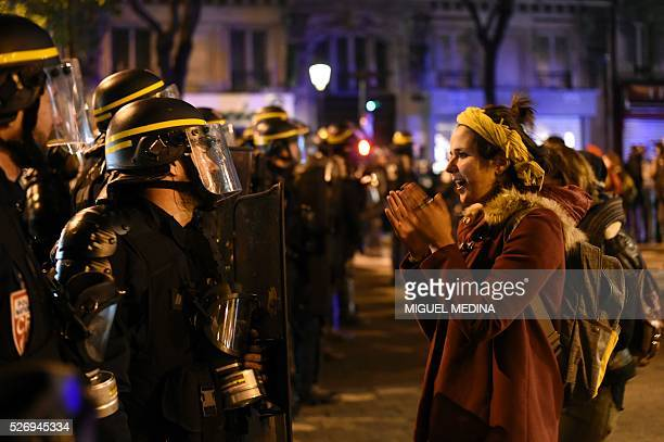 A woman faces French anti riot policemen as they block the access to the Place de la Republique after protesters taking part in the Nuit Debout...