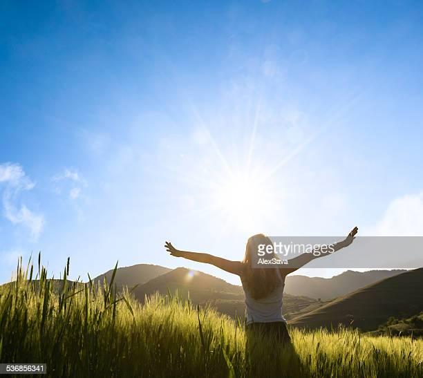 Frau vor der Sonne mit Händen outstratched