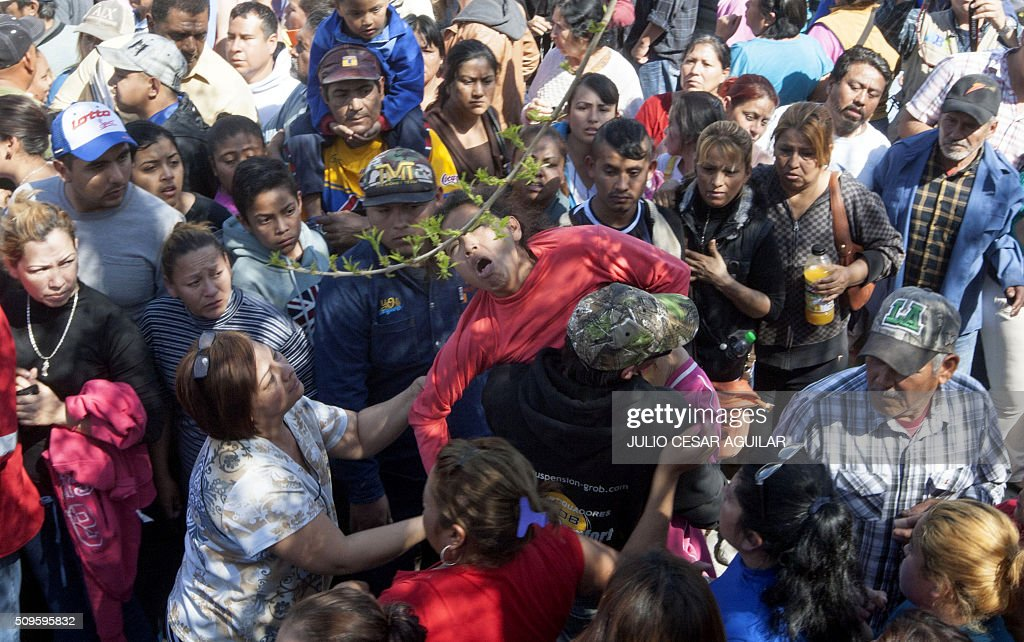 A woman faints among relatives of inmates as they gather outside the Topo Chico prison -where a riot took place- in Monterrey, Mexico on February 11, 2016. Riot police and ambulances were deployed at the Topo Chico prison as smoke billowed from the facility. At least 49 inmates were killed in a Mexican prison brawl on Thursday, as prisoners fought with bats, sticks and blades and ignited a fire in the overcrowded penitentiary. AFP PHOTO / JULIO CESAR AGUILAR / AFP / Julio Cesar Aguilar