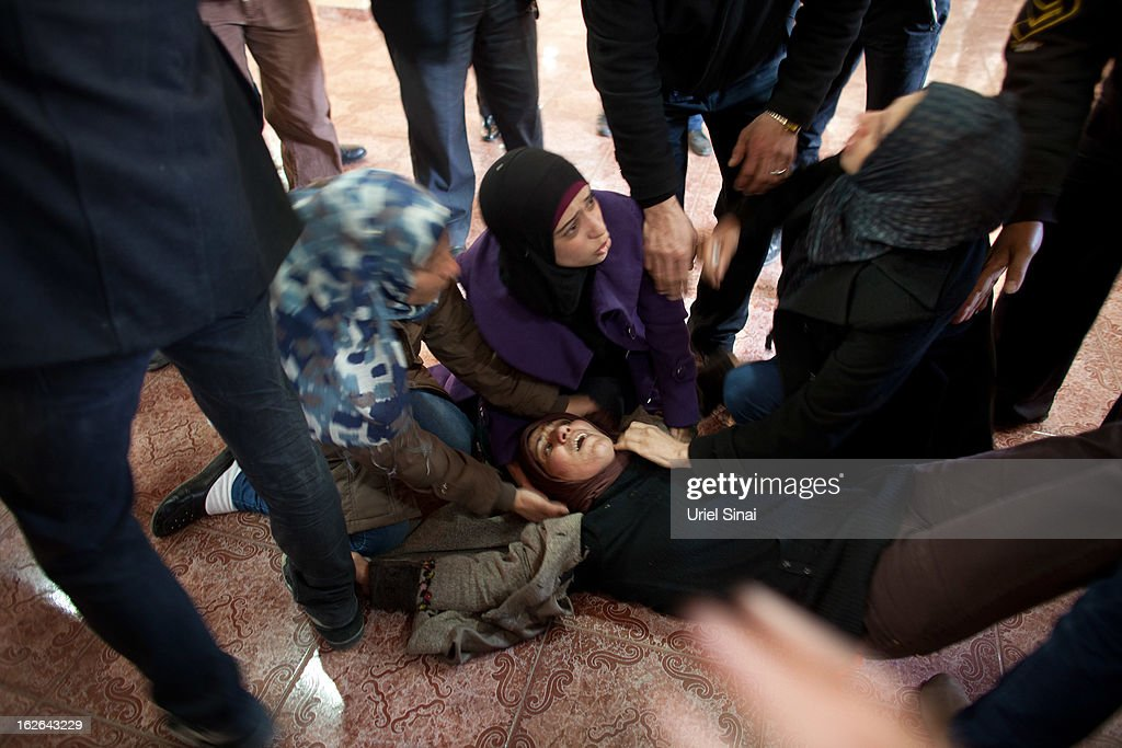 A woman faints as during the funeral for Palestinian Arafat Jaradat on February 25, 2013 in the village of Saair in the West Bank. According to reports, Jaradat died while in Israeli custody under disputed circumstances, with Palestinian officials saying an autopsy showed he was tortured.