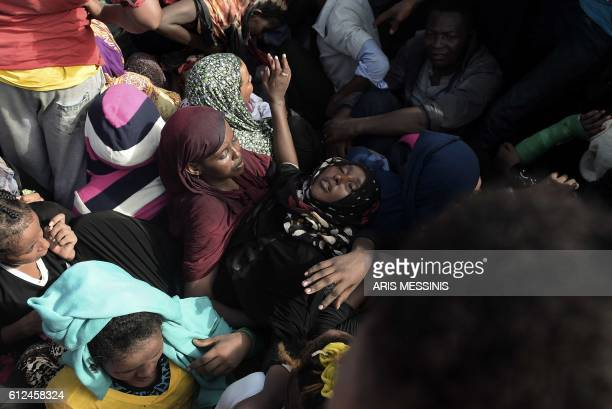 TOPSHOT A woman faints while refugees and migrants wait to be rescued by members of Proactiva Open Arms NGO in the Mediterranean Sea some 12 nautical...