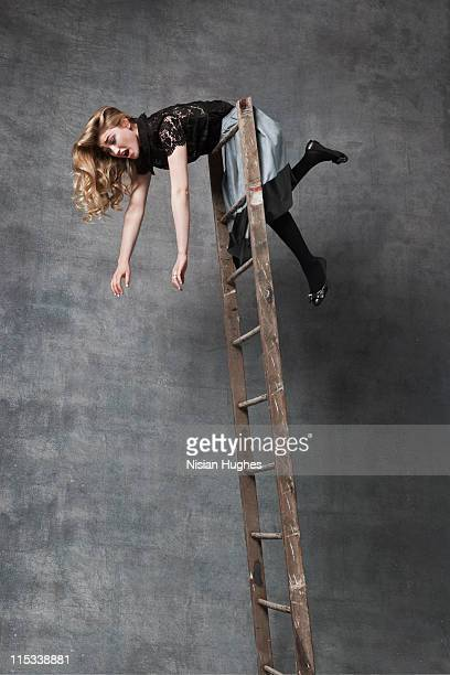 Woman falling over top of ladder