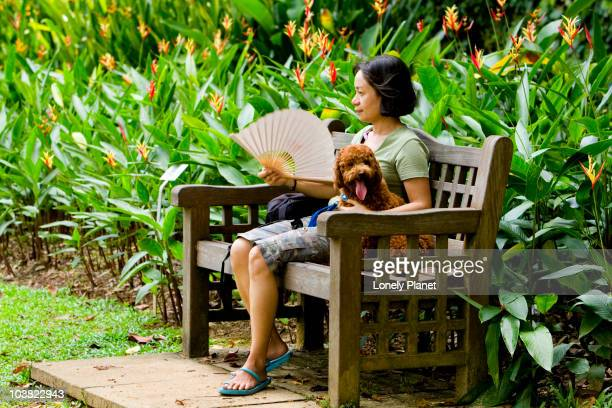 Woman fanning herself with dog on bench at Singapore Botanic Gardens.