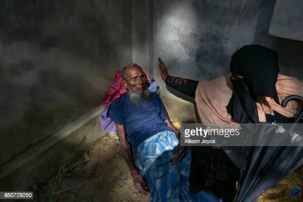 COX'S BAZAR BANGLADESH SEPTEMBER 21 A woman fans her husband in the Balukhali Rohingya refugee camp on September 21 2017 in Cox's Bazar Bangladesh...