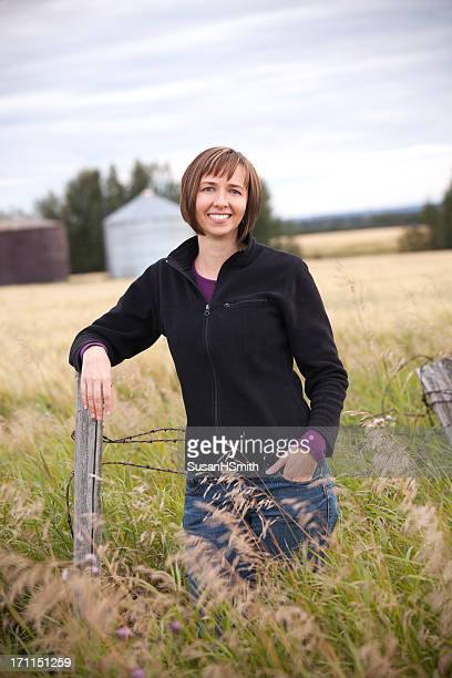 A woman farmer standing in the middle of a grassy field