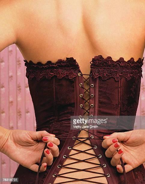 Woman fastening corset