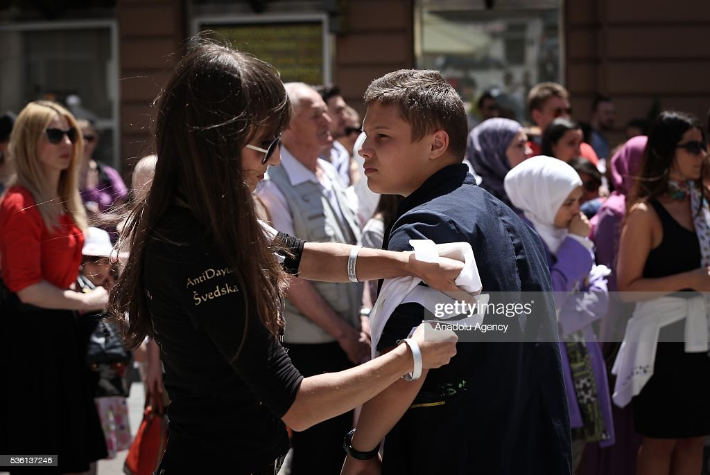 A woman fastens a white ribbon to boy's arm during a commemoration ceremony at the Cathedral of Jesus' Heart for non-Serb civilians killed in the war on the territory of western town of Prijedor, in Sarajevo, Bosnia and Herzegovina on May 31, 2016.
