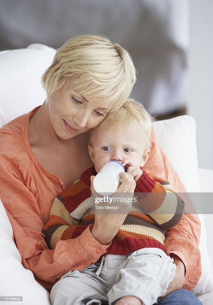 Woman feeding baby boy with bottle : Stock Photo