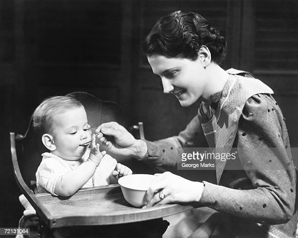 Woman feeding baby (6-9 months) sitting on high chair (B&W)