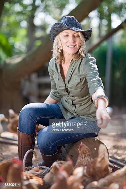 Frau Füttern Hühner auf dem Bauernhof