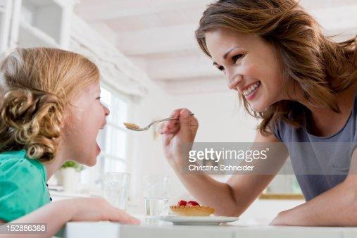 Woman feeding daughter breakfast