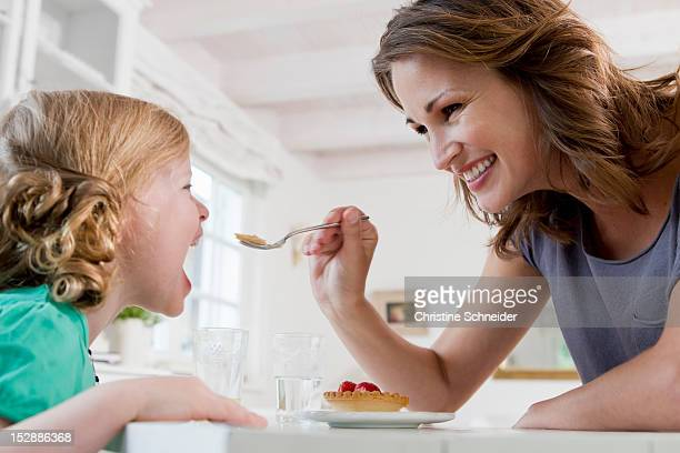 Woman feeding daughter breakfast