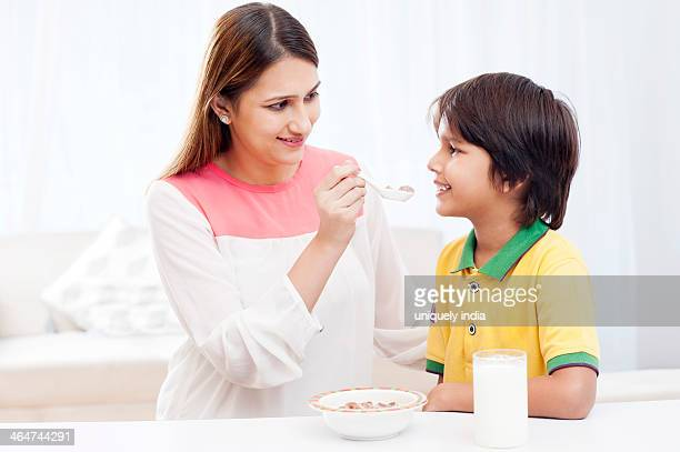 Woman feeding food to her son